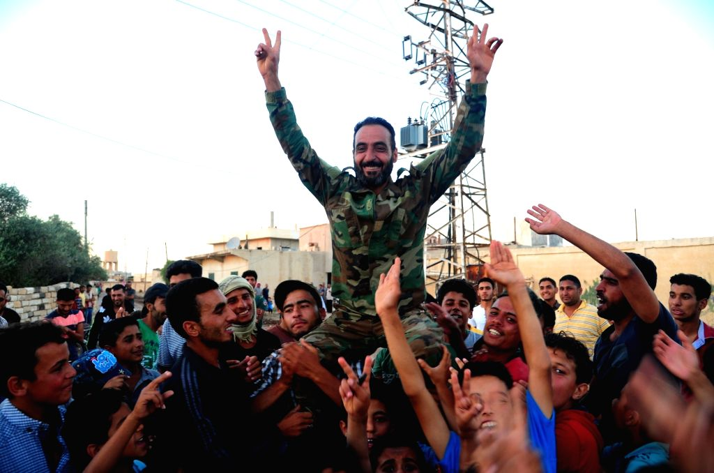 DARAA, July 9, 2018 - People carry a Syrian soldier as they welcome Syrian army in the Kharab al-Shahem town in the western countryside of Daraa province in southern Syria on July 8, 2018. The Syrian ...