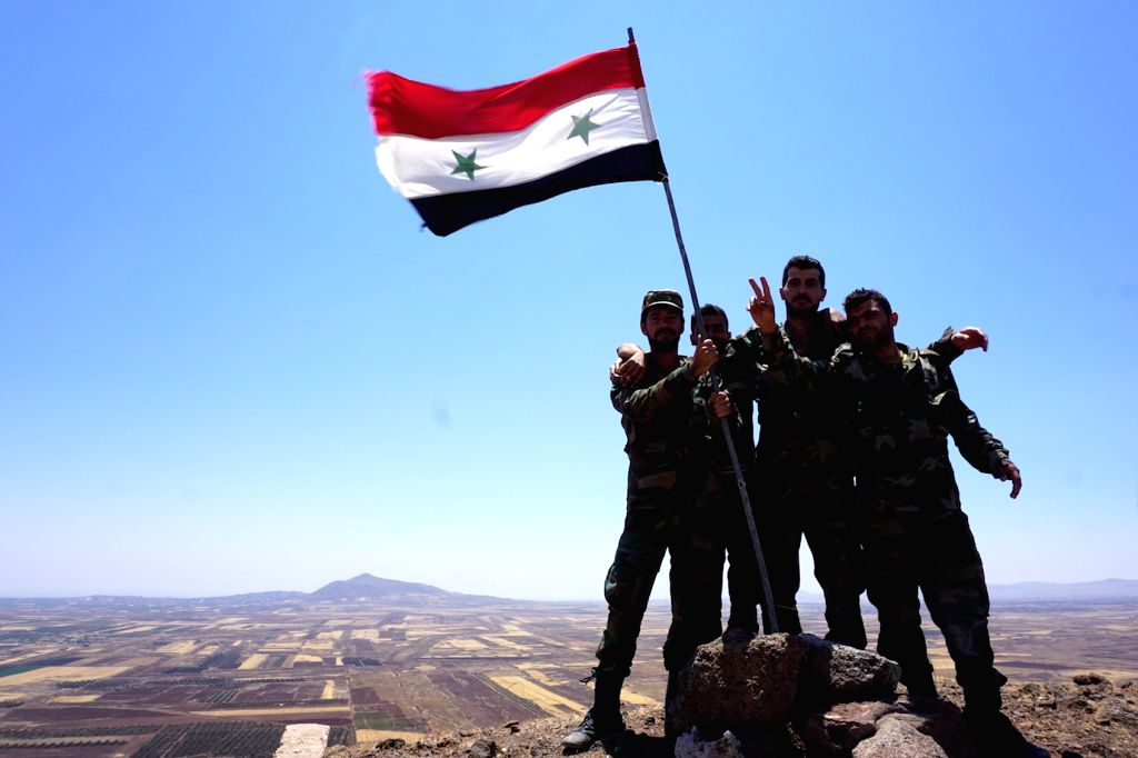 DARAA (SYRIA), July 18, 2018 Syrian soldiers pose for photos with a Syrian flag on Al-Mal Hill, near the newly-captured town of Al-Mal in the northwestern countryside of Daraa province in ...