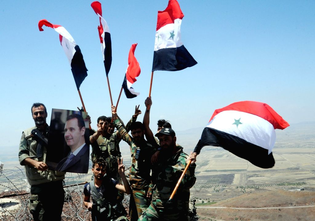 DARAA (SYRIA), July 19, 2018 Syrian soldiers hold Syrian flags on the Tal al-Harrah in the northwestern countryside of Daraa Province, Syria, July 19, 2018. The Syrian army on Monday ...