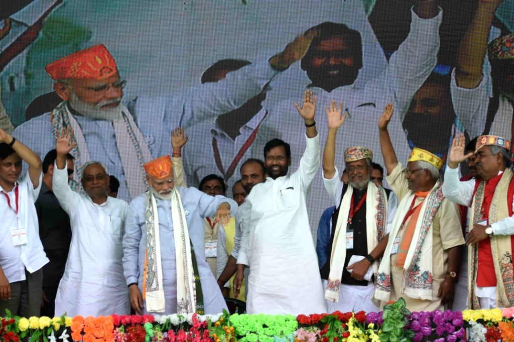 Darbhanga: Prime Minister Narendra Modi accompanied by Bihar Chief Minister Nitish Kumar, Deputy Chief Minister Sushil Kumar Modi and Union Minister Ram Vilas Paswan, waves to crowd during a public rally in Darbhanga, Bihar, on April 25, 2019. (Photo - Narendra Modi, Nitish Kumar and Sushil Kumar Modi