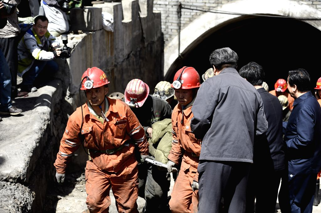 Rescuers carry a miner out of well at Jiangjiawan mine in Datong, north China's Shanxi Province, April 21, 2015. The death toll of the coal mine flood accident has ...