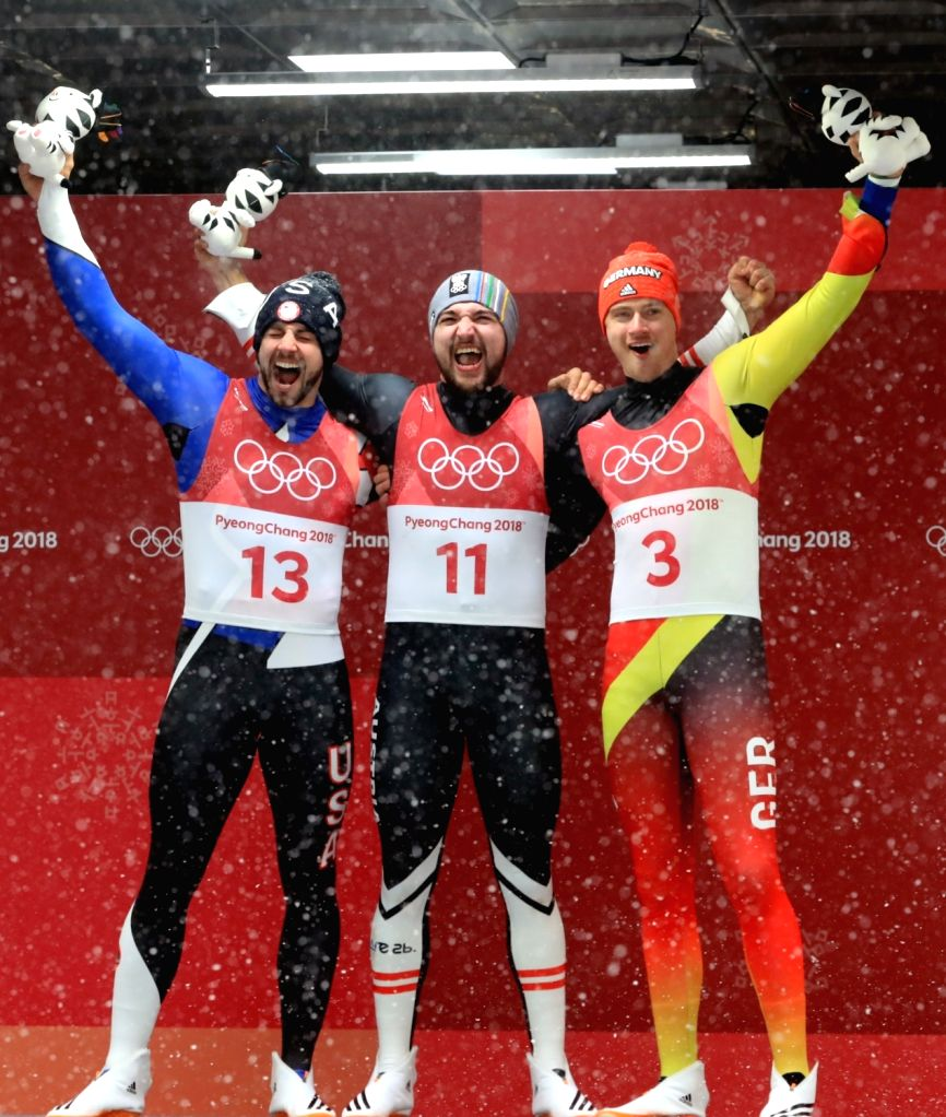 David Gleirscher of Austria (C), Chirs Mazdzer (L) of the United States and Johannes Ludwig of Germany celebrate after crossing the finish line to win gold, silver and bronze medals, ...