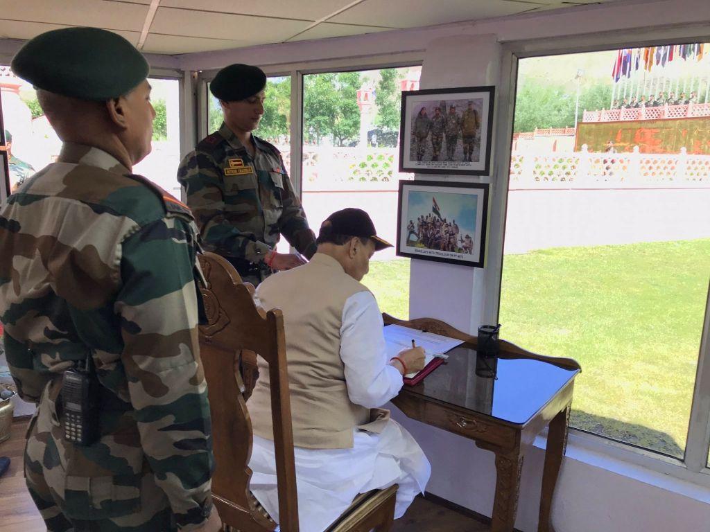 Defence Minister Rajnath Singh signs the Visitors' Book of Kargil War Memorial in Dras of Jammu and Kashmir's Kargil district, on July 20, 2019. - Rajnath Singh
