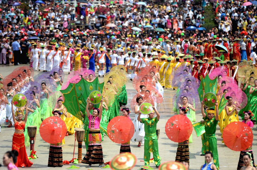 Local residents perform at the opening ceremony of the water-sprinkling festival in Mangshi City of Dehong Dai-Jingpo Autonomous Prefecture, southwest China's ...