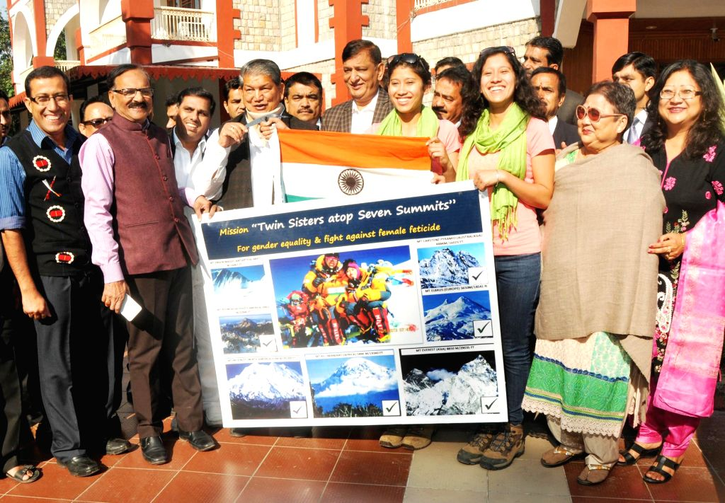 Uttarakhand Chief Minister Harish Rawat hands over the Indian flag to Tashi and Nungshi Malik, 23-year-old look-alike twin sisters who are set to scale Mt Vinson in Antarctica, in Dehradun . - Harish Rawat