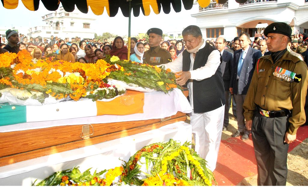 Uttarakhand Chief Minister Harish Rawat lays wreath on the body of martyr Ajay Vardhan Tomar who was killed in a encounter with militants in Kupwara of Jammu and Kashmir at his residence in - Harish Rawat