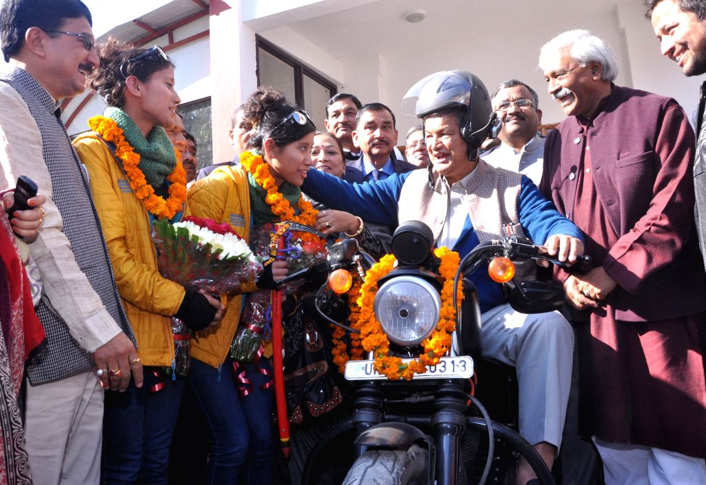 Uttarakhand Chief Minister Harish Rawat rides a bike as he welcomes Tashi and Nungshi Malik, 23-year-old look-alike twin sisters who returned back after scaling Mt Vinson in Antarctica, in .