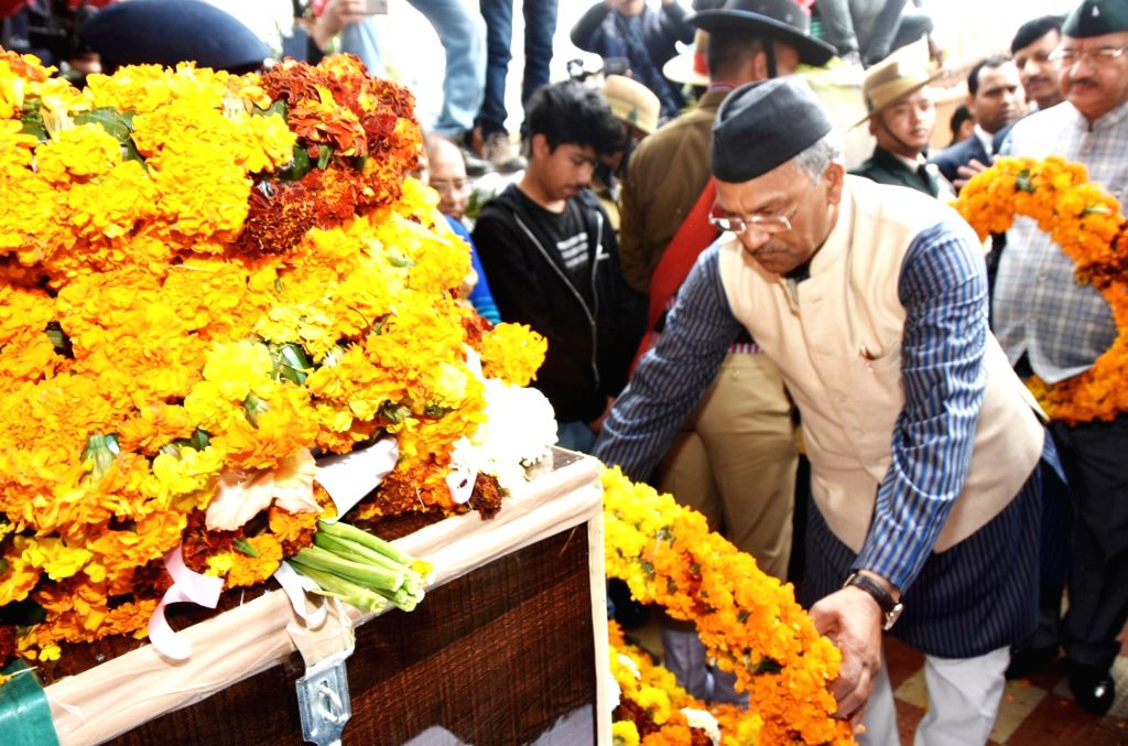 Dehradun: Uttarakhand Chief Minister Trivendra Singh Rawat pays tribute to Major Chitresh Singh Bisht, who lost his life while defusing a landmine along the Line of Control (LoC) in Rajouri district of Jammu and Kashmir; in Dehradun on Feb 18, 2019.  - Trivendra Singh Rawat and Chitresh Singh Bisht