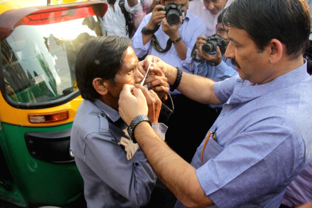 Delhi BJP chief Manoj Tiwari distributes masks to an auto rickshaw driver in New Delhi on Oct 29, 2018.