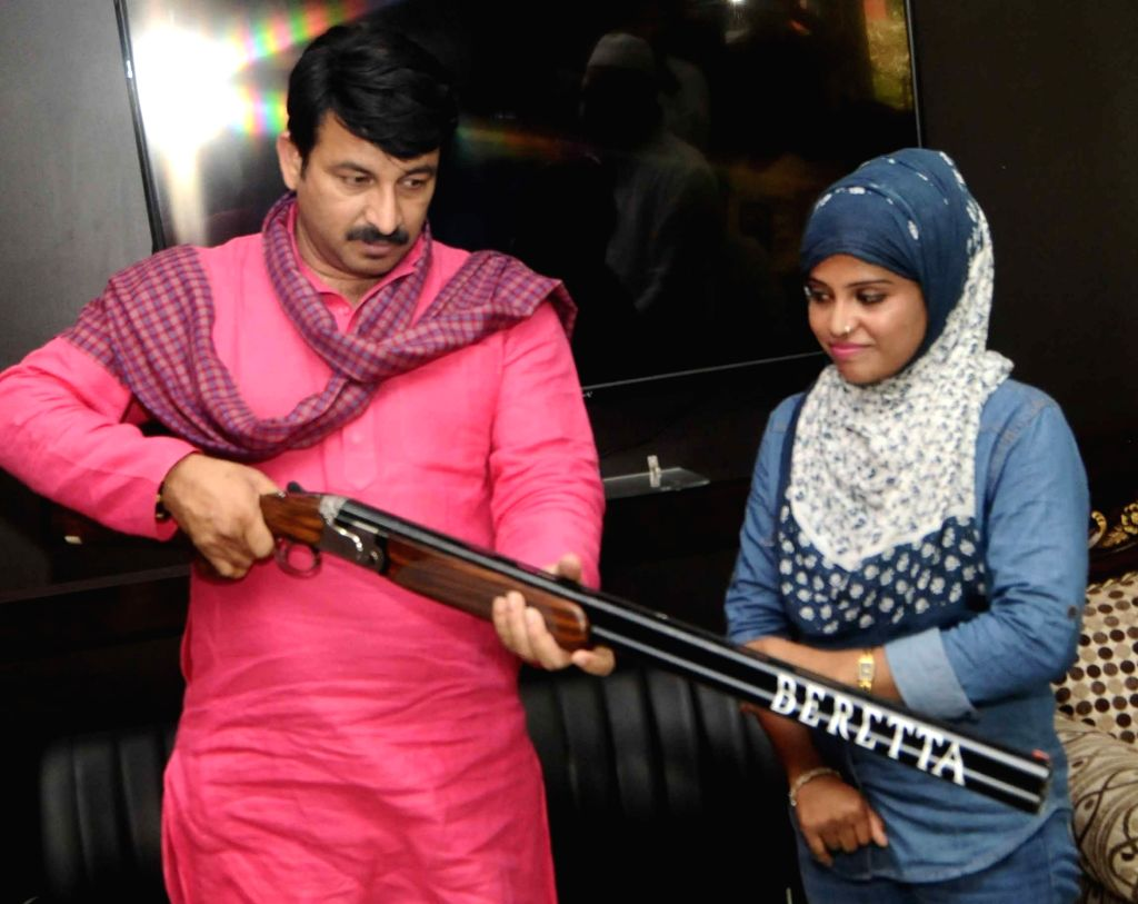 Delhi BJP chief Manoj Tiwari felicitates national shooter Ayesha Falaq, who rescued her brother-in-law from kidnappers by shooting at the abductors in New Delhi on June 27, 2017.