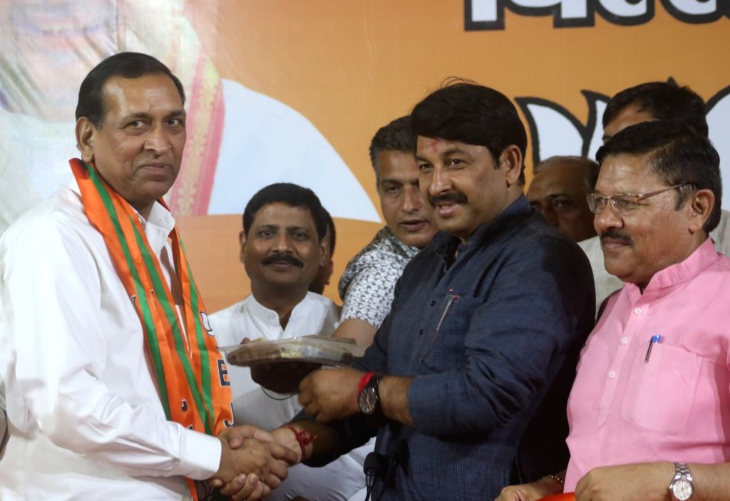 Delhi BJP chief Manoj Tiwari welcomes Former Delhi Minister and Congress MLA Raj Kumar Chauhan into the party, at the BJP headquarter in New Delhi on May 11, 2019. - Kumar Chauhan
