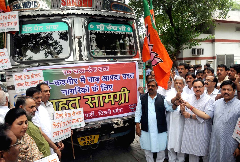 Delhi BJP chief Satish Upadhyay and other party leaders flag-off a truck carrying relief material for flood affected people of Jammu and Kashmir in New Delhi on Sept 9, 2014. - Satish Upadhyay