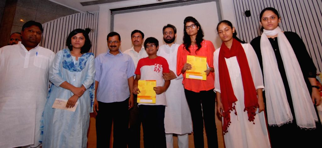 Delhi Chief Minister Arvind Kejriwal presents Rs 1 crore cheque to slain NDMC officer MM Khan's family and 50-50 lakh fixed deposits for the children of NIA inspector Tanzil Ahmad during a ... - Arvind Kejriwal