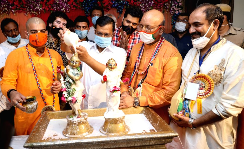 Delhi Chief Minister Arvind Kejriwal washes the idol of Lord Krishna with milk during Krishna Janmashtami celebrations at the ISKCON Temple in New Delhi on Aug 12, 2020. - Arvind Kejriwal