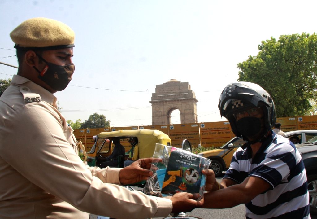 Delhi Civil Defence health workers distribute Masks, Hand Sanitizer for people organized by New Delhi District Administration at India Gate in new Delhi on Saturday March 27, 2021.