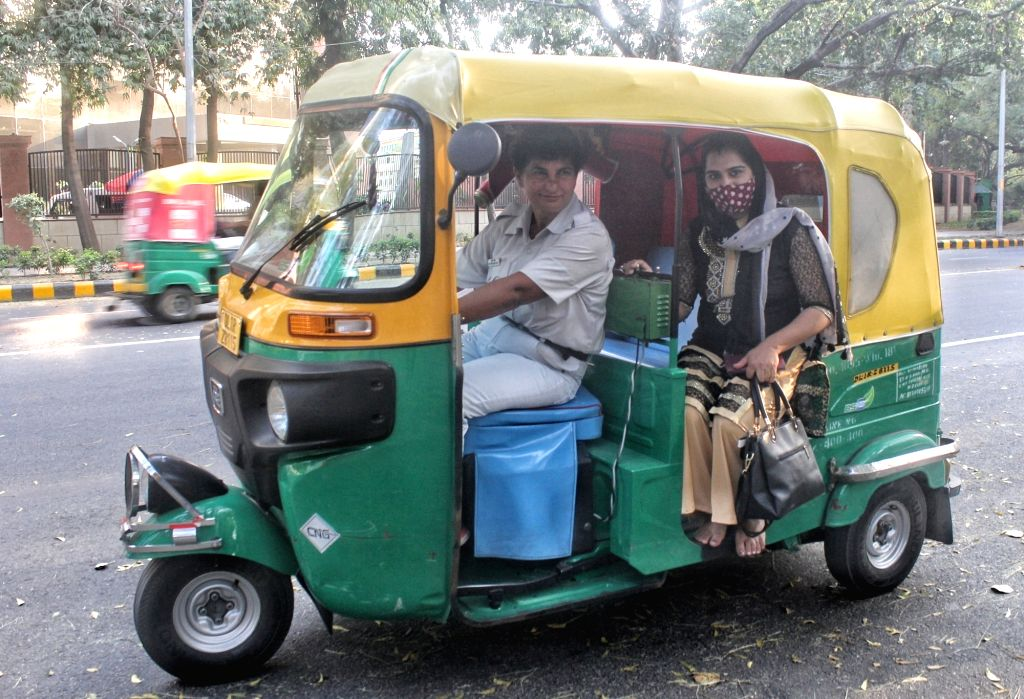 Delhi first woman auto driver Sunita Choudhary, age 40,, poses with her auto and spending her free time with her auto drivers friend on the occasion of world womens day 2021. she is from meerut UP, ... - Sunita Choudhary