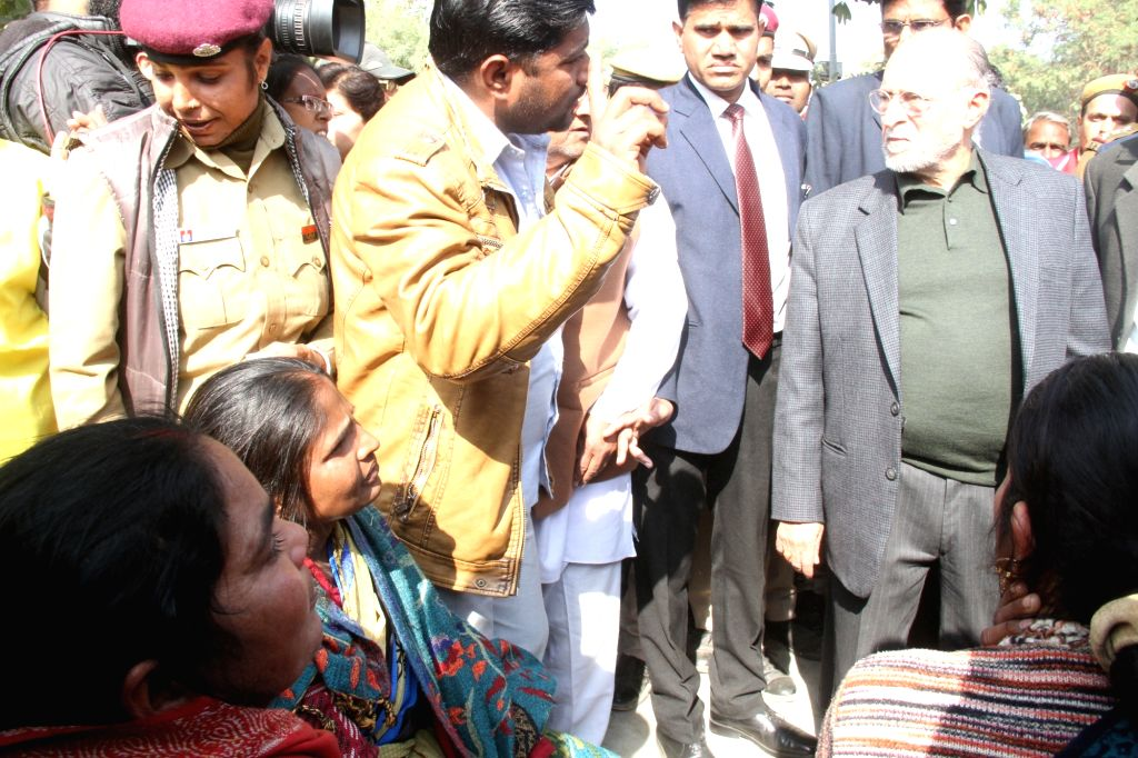 Delhi Lieutenant Governor, Anil Baijal talks to the relatives of the victims of Bawana factory fire outside B R Ambedkar Hospital in New Delhi on Jan 21, 2018. As many as 17 people, ...