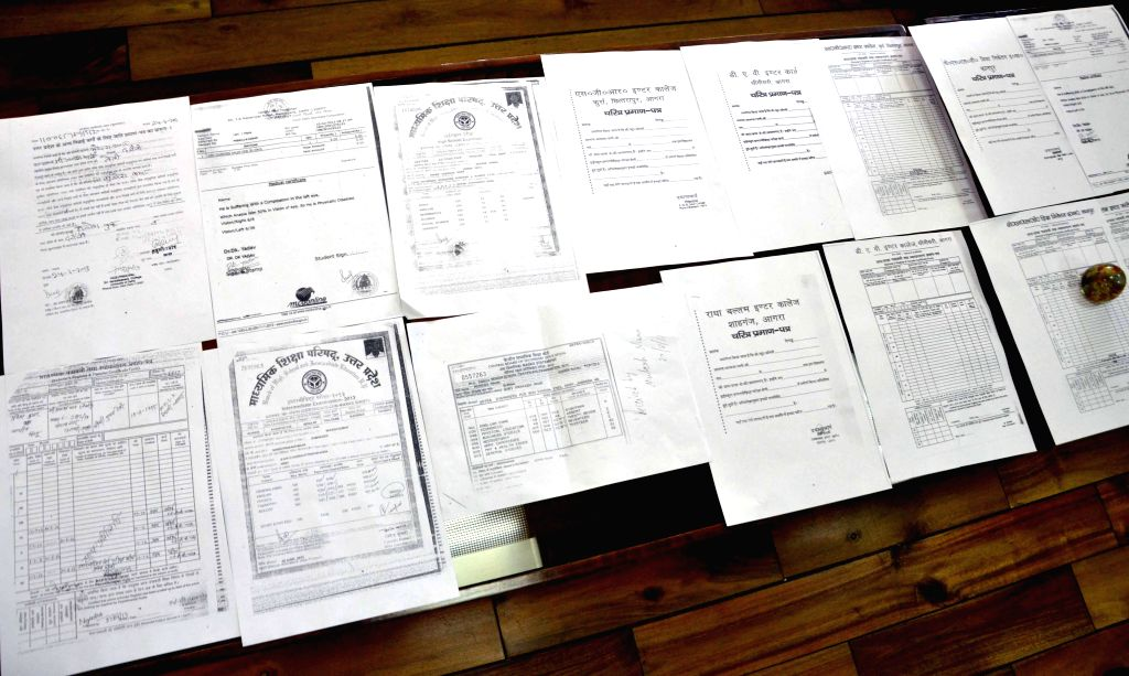 Delhi Police Crime Branch officials display forged documents recovered from the three persons arrested in connection with forgery of documents to get admissions in prestigious colleges of Delhi at ...