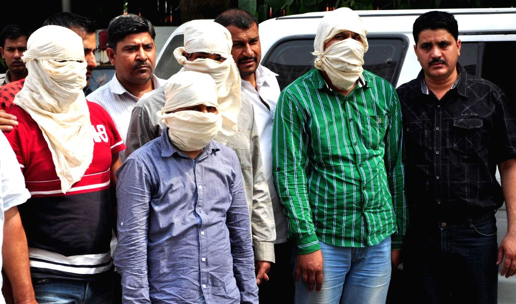 Delhi Police crime branch present before media persons allegedly involved in a kidnap- robbery case in New Delhi on May 2, 2014.