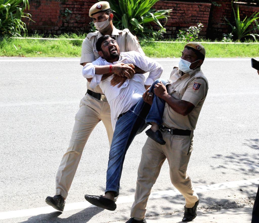 Delhi police personnel detain a Youth Congress activist  protesting against Sunday's killing of four farmers in Uttar Pradesh Lakhimpur Kheri in New Delhi on Monday October 04 , 2021