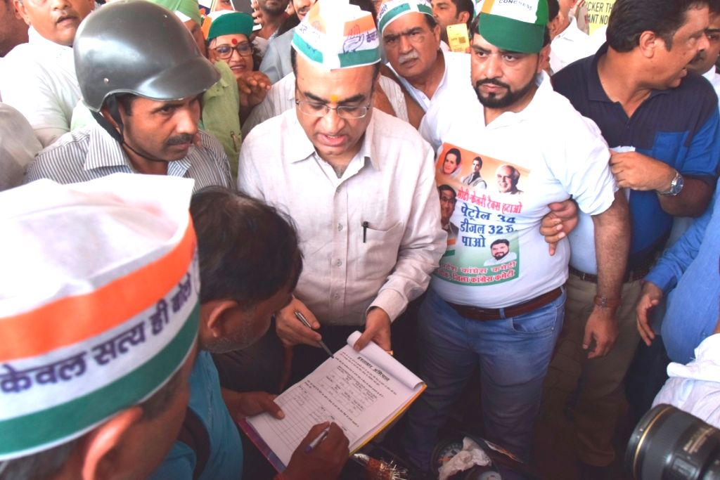 Delhi Pradesh Congress Committee (DPCC) president Ajay Maken collects signatures during a campaign at petrol pumps across the city to protest against the fuel price hikes and collect 10 ... - Narendra Modi and Arvind Kejriwal