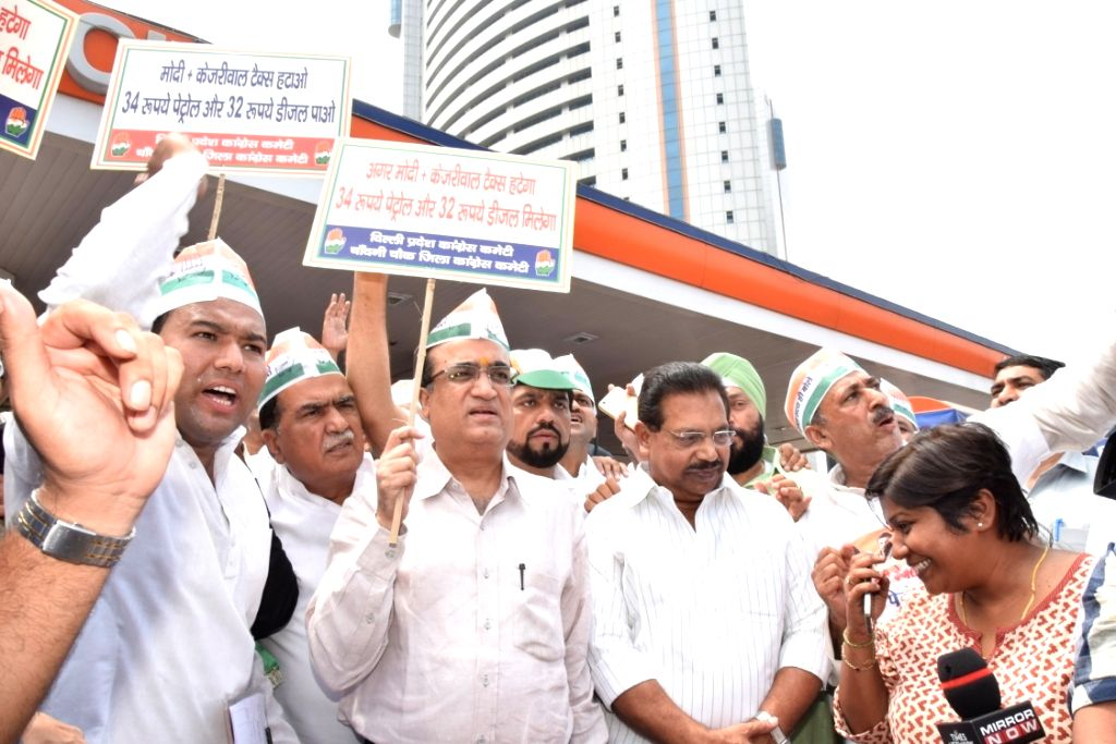 Delhi Pradesh Congress Committee (DPCC) president Ajay Maken during a campaign at petrol pumps across the city to protest against the fuel price hikes and collect 10 lakh signatures which ... - Narendra Modi and Arvind Kejriwal