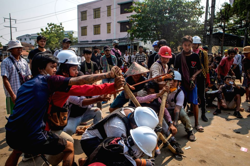 Demonstrators use a self-made catapult during clashes with police at a demonstration against the military coup and the detention of civilian leaders. Photo: Thuya Zaw/ZUMA Wire/dpa/IANS