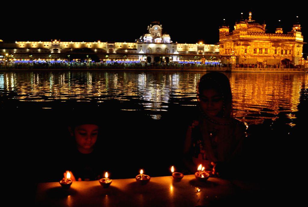Devotee light up candles at the Golden Temple on the occasion of 'Gurta Gaddi Diwas' of the sixth Sikh Guru, Guru Hargobind Sahib in Amritsar on May 27, 2019.