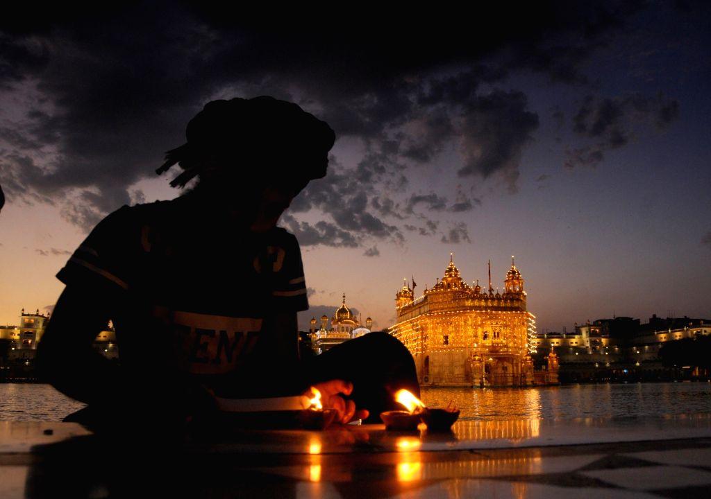 Devotee light up diyas at the Golden Temple on the occasion of Sikhs third Guru, Guru Amar Das Ji's birth anniversary in Amritsar on May 6, 2020.