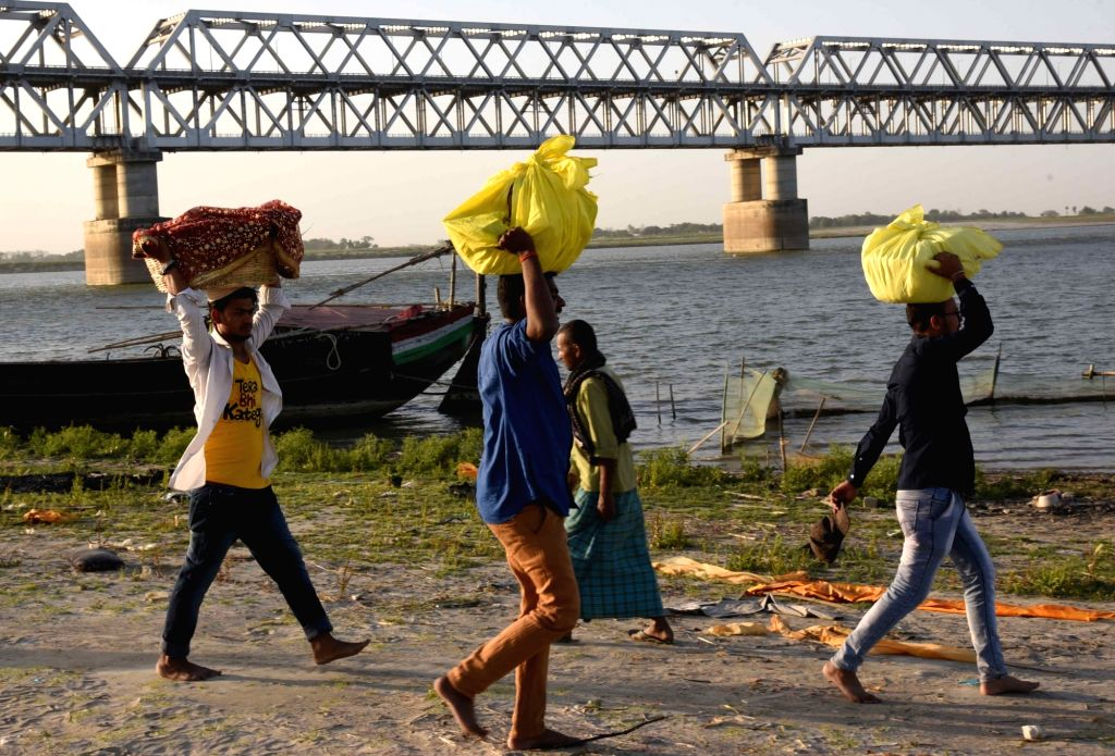 Devotees arrive to perform rituals on the banks of the Ganga river during Chaiti Chhath celebrations amid countrywide lockdown imposed to contain the spread of novel coronavirus, in Patna on ...