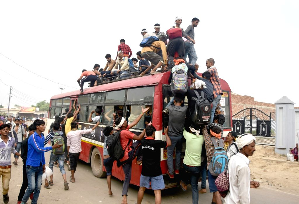 Devotees board an overcrowded bus as they leave for Mudiya Mela in Govardhan near Uttar Pradesh's Mathura on July 16, 2019.