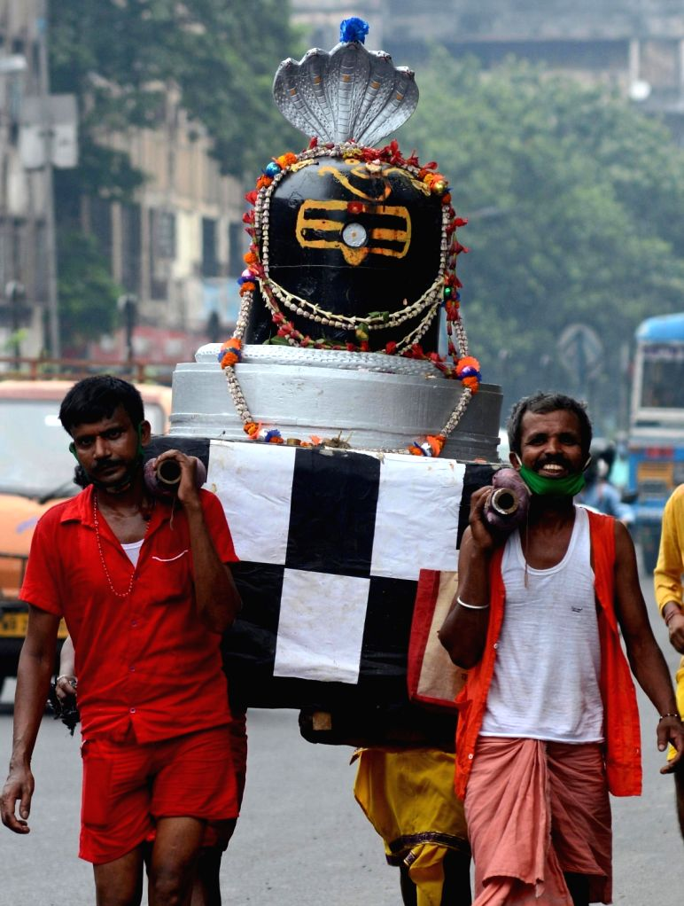 Devotees carry a huge Shiva Lingam on their shoulders to a temple on the occasion of 'Sawan Somwar' in Kolkata on Aug 3, 2020.