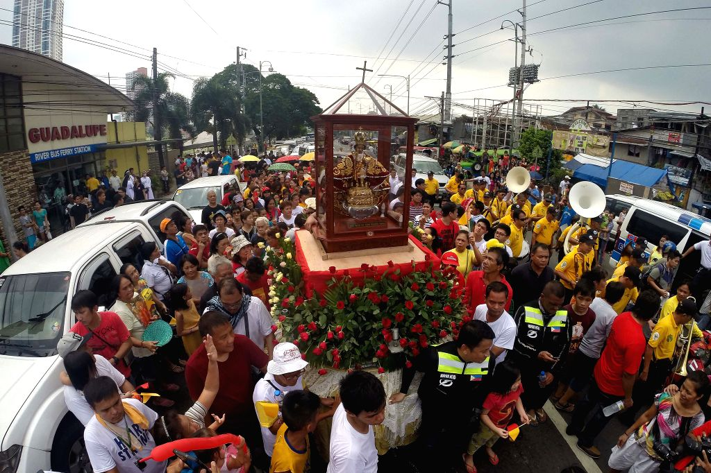 Devotees carry the image of the Santo Nino de Cebu during a fluvial procession along Pasig River in celebration of the 450th anniversary of the finding of the image ...
