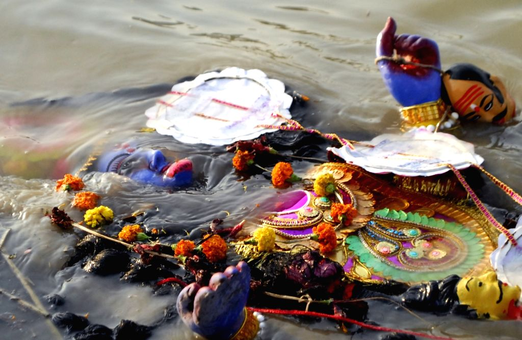 Devotees immerse an Idol of Goddess Kali at River of Ganga in Kolkata, on November 15, 2020.