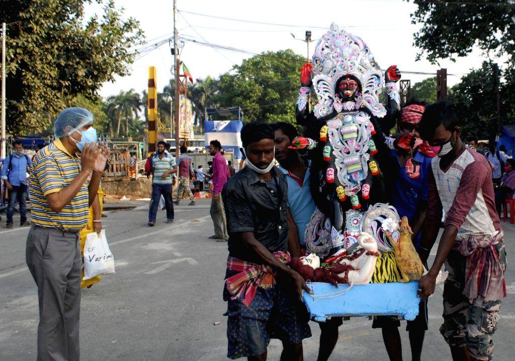Devotees immerse an Idol of Goddess Kali at River of Ganga in Kolkata, on November 15, 2020.