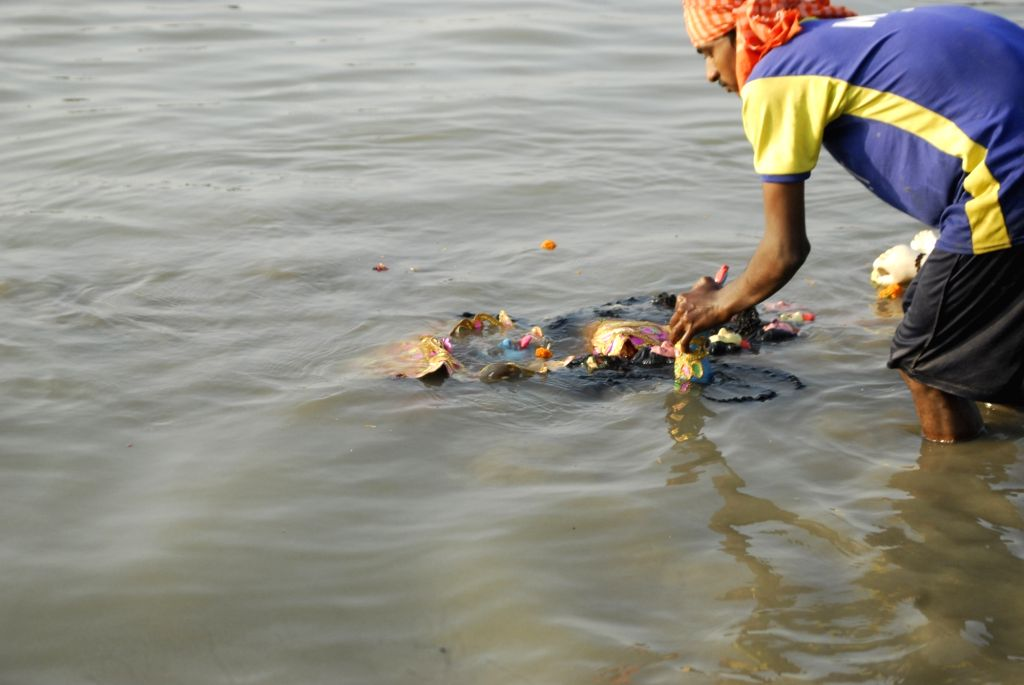 Devotees immerse an idol of Goddess Kali into river Ganga in Kolkata, on Nov 16, 2020.