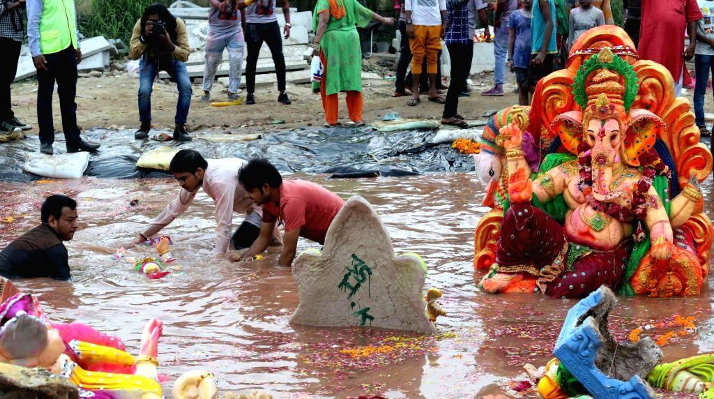 Devotees immerse Ganesh idols into a artificial pond, especially dug up for Ganpati visarjan, in New Delhi on Sep 12, 2019.