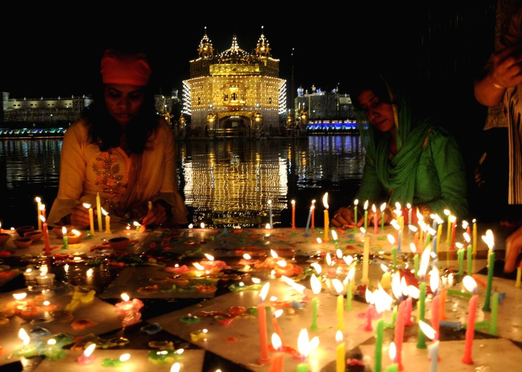 Devotees light candles at the Golden Temple that has been illuminated on the occasion of 550th birth anniversary of Guru Nanak Dev, in Amritsar on Nov 12, 2019. - Nanak Dev