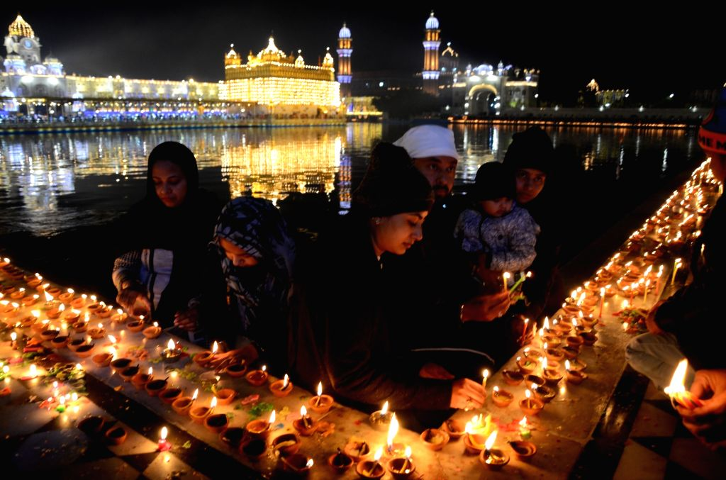 Devotees light up candles and earthen lamps at the illuminated Golden Temple on Guru Nanak Jayanti, in Amritsar on Nov 30, 2020.