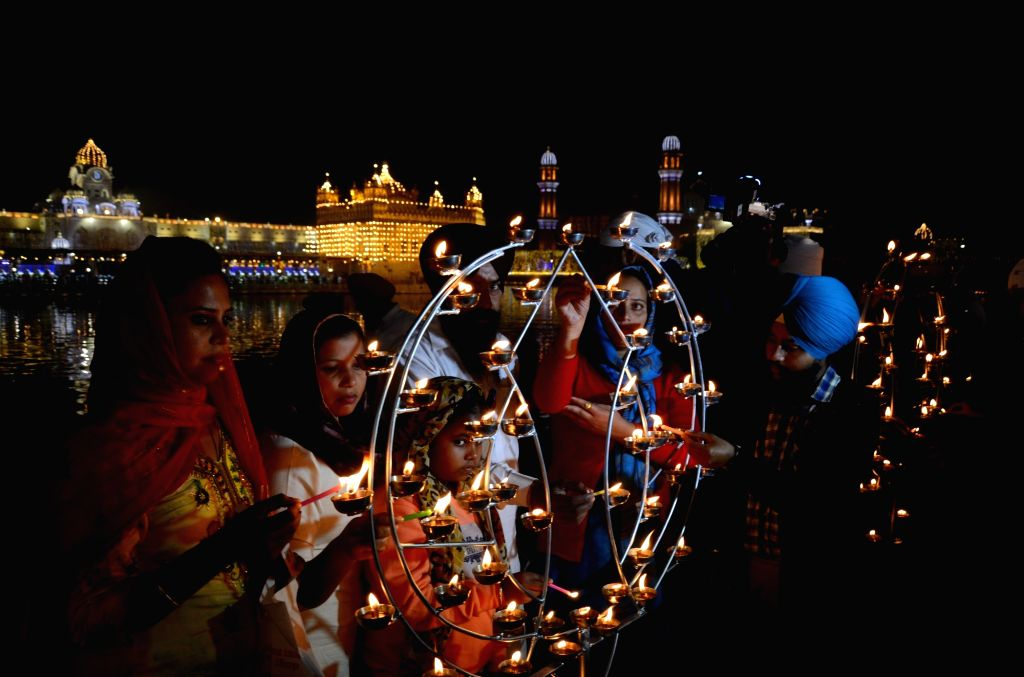 Devotees light up diyas and witnesses fireworks at Golden Temple on the occasion of 'Bandi Chhor Divas' , a Sikh festival coinciding with Diwali, in Amritsar on November 14, 2020.