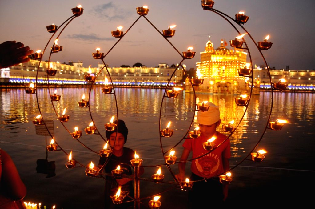 Devotees lights lamps at the Golden Temple on 'Parkash Purab of Sri Guru Granth Sahib' at the Golden Temple in Amritsar on Sept 10, 2018.