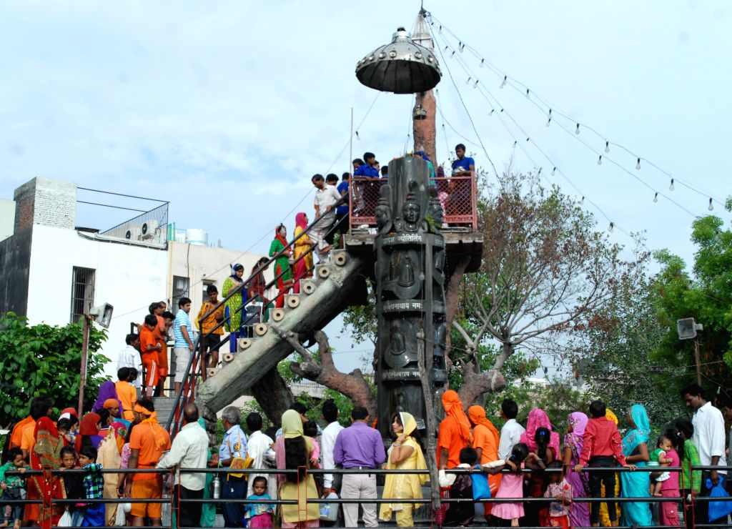 Devotees of lord Shiva offer milk to Shivalings during holy month of Sawan in New Delhi on July 25, 2014.