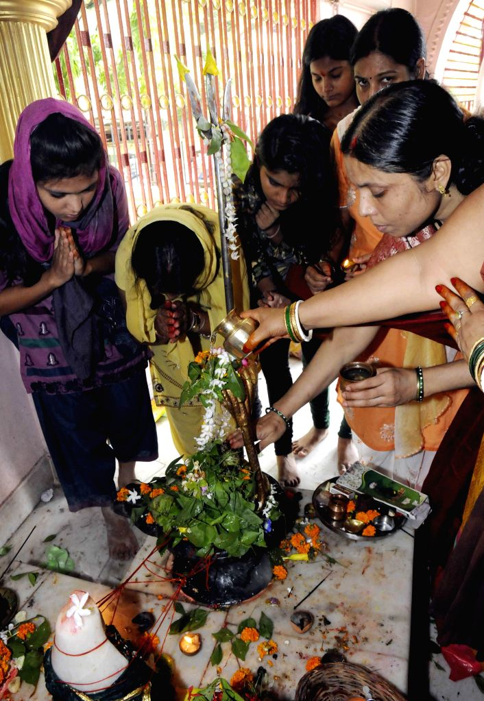 Devotees offer prayers at a Shiva temple during the holy month of `Sawan` in Patna on July 28, 2014.