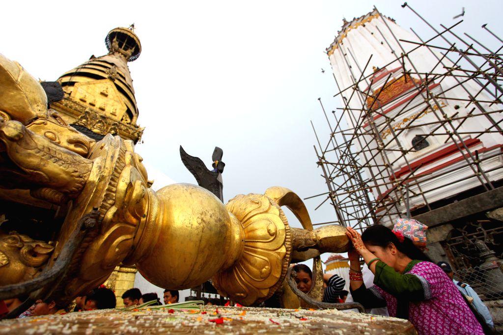 Devotees offer prayers at Swayambhunath in Kathmandu, Nepal, Aug. 15, 2015. Swayambhunath Stupa, a UNESCO world heritage site of Nepal, is opened to public after ...