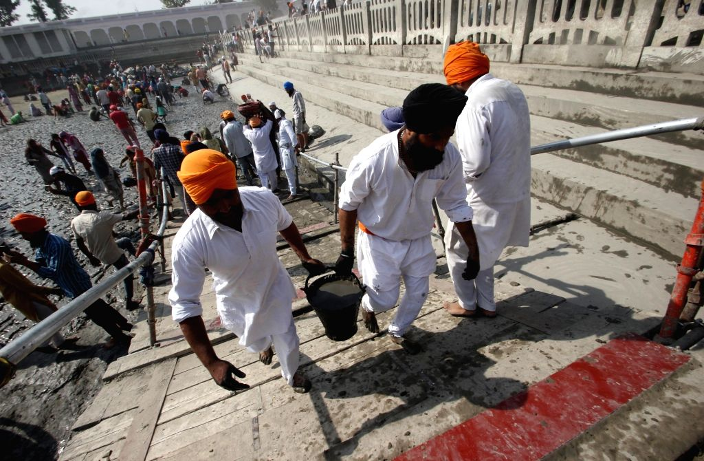 Devotees perform Kar Seva as they participate in cleansing the pond of Gurudwara Baba Budda Sahib in Amritsar on March 31, 2018.
