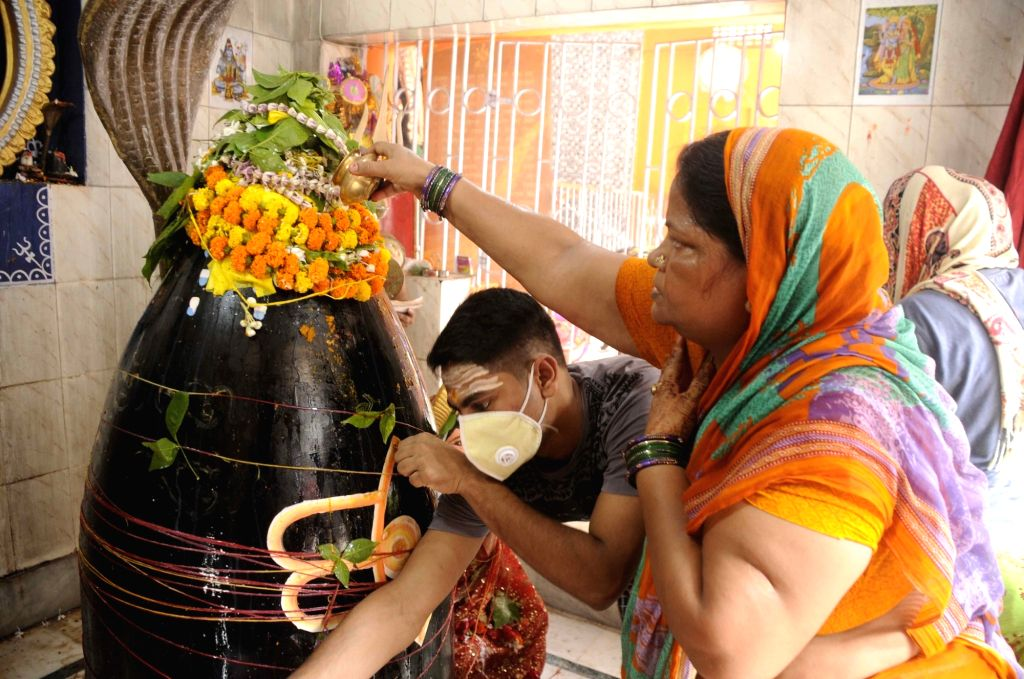 Devotees perform rituals as they offer prayers to Lord Shiva on the first Monday of Shravan, at the Kankarbagh Shiv Temple in Patna on July 6, 2020. After the celebration of Guru Purnima on ...
