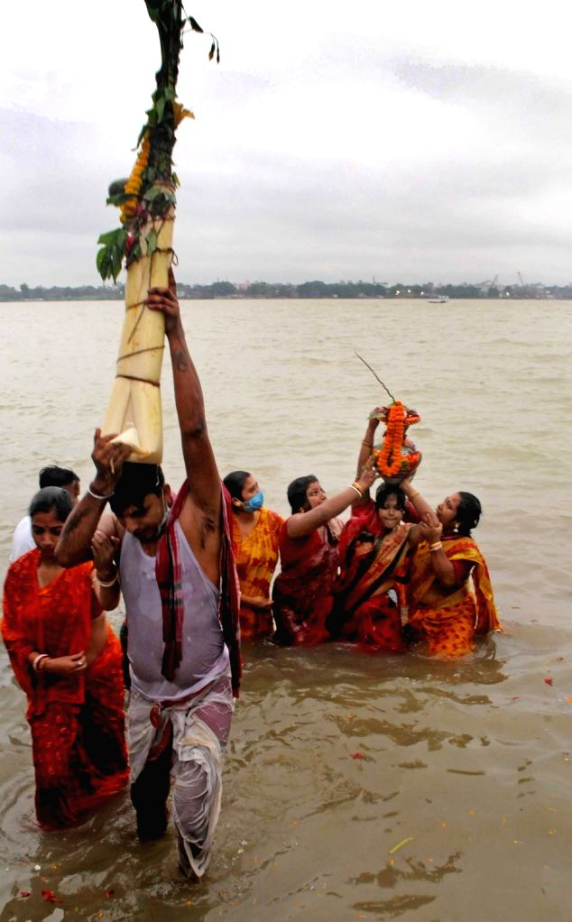 Devotees perform rituals on the banks of Ganga river during Nabapatrika Snan on Maha Saptami during Durga Puja celebrations, in Kolkata on Oct 23, 2020. On this day the rituals start before ...