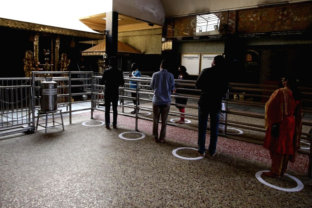 Devotees practise social distancing as they queue up at a temple to offer prayers after the Tamil Nadu Government permitted the reopening of the places of worship as part of several ...