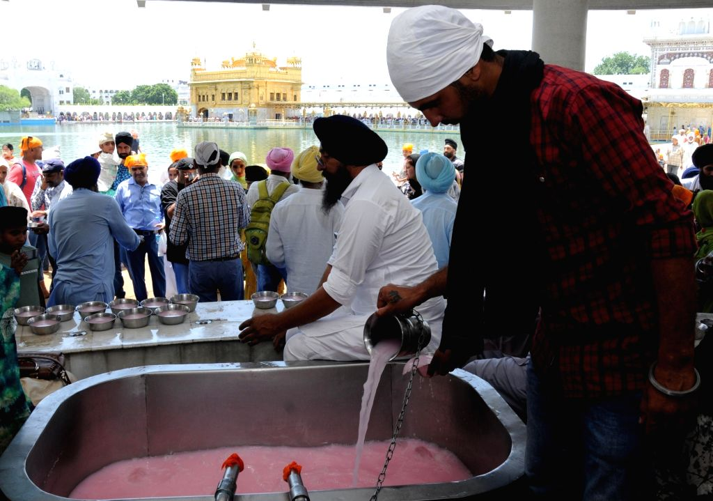 Devotees prepare sweetened water to be distributed among people on the martyrdom day of Guru Arjan Dev, at the Golden Temple in Amritsar, on June 7, 2019. - Arjan Dev