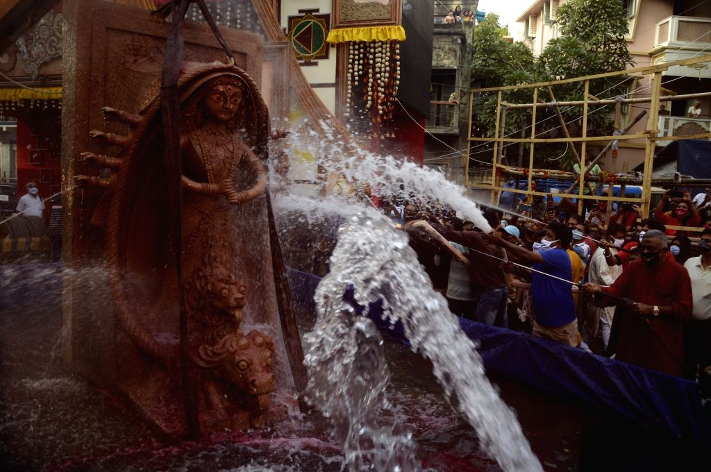 Devotees spray water on an idol of Goddess Durga during Durga idol immersion on Vijayadashami, outside a community puja pandal, in Kolkata on Oct 26, 2020.